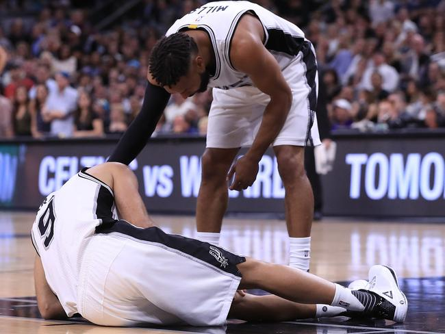 Patty Mills checks on Tony Parker after the starting guard went down injured.