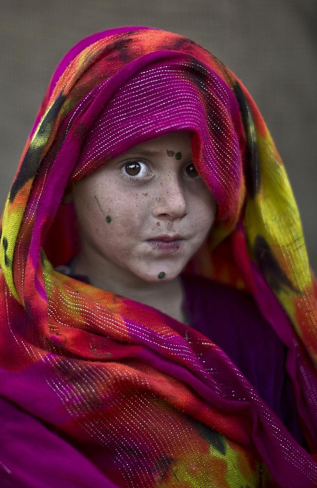 Afghan refugee girl, Robina Haseeb, 5, poses for a picture, while playing with other children in a slum on the outskirts of Islamabad, Pakistan.