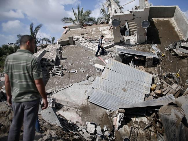 Wiped out ... Palestinian men inspect their destroyed house following an Israeli air strike in Gaza City on July 15. Picture: AFP