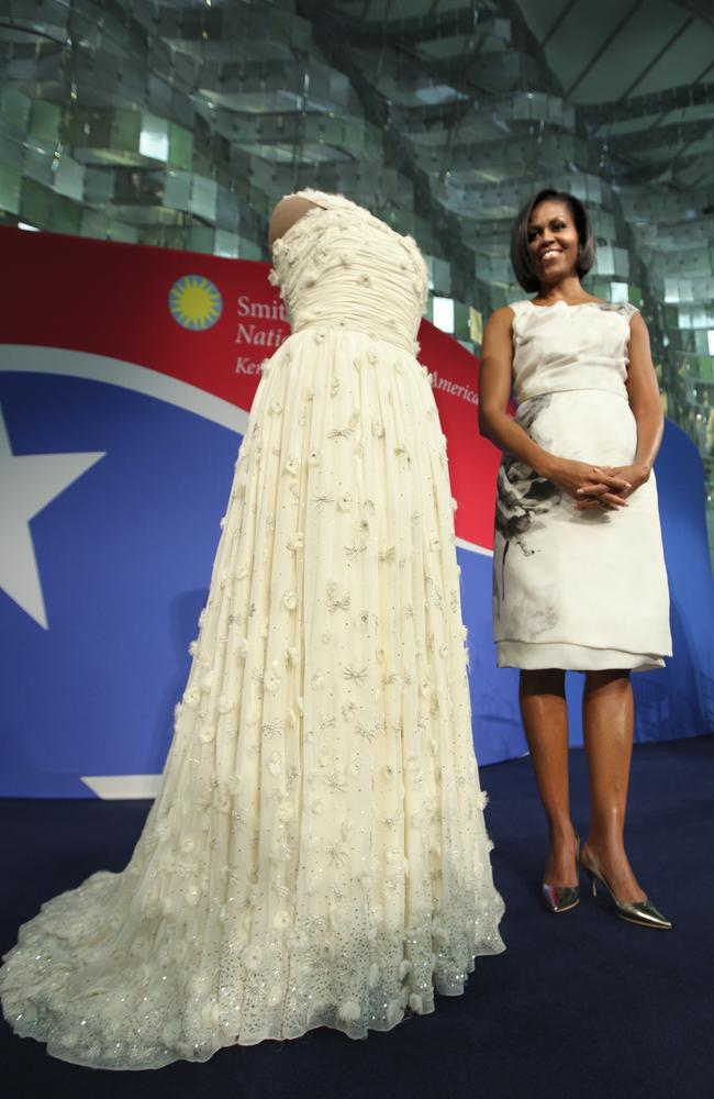 Michelle Obama, pictured in 2011, standing with the gown that she wore to the 2009 Inaugural Ball. Picture: J. Scott Applewhite/AP