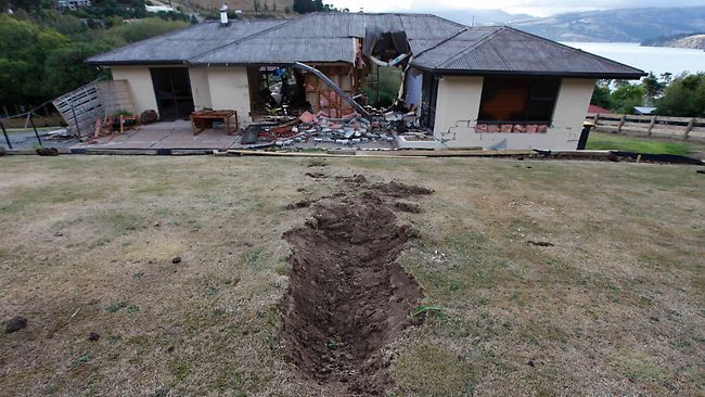 A hole, created by a giant boulder which crashed through a house during Tuesday's earthquake, is seen near Lyttelton, on the outskirts of Christchurch, New Zealand, Thursday, Feb. 24, 2011. Tuesday's magnitude-6.3 temblor caused extensive damage, and killed dozens of people in the city. (AP Photo/Mark Baker)