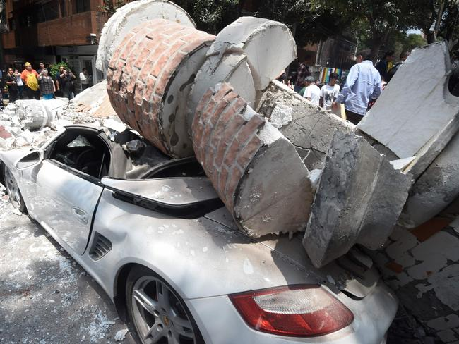 A car is crushed by a falling structure in quake-hit Mexico City. Picture: AFP/Alfredo Estrella