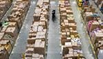 "Workers prepare customer orders for dispatch as they work around goods stored inside an Amazon.co.uk fulfillment centre in Peterborough, central England, on November 15, 2017. Shops could be seeing the effect of consumers postponing purchases until ""Black Friday"" on November 24, 2017, a day of sales in the United States that has become increasingly popular in Britain. / AFP PHOTO / CHRIS J RATCLIFFE"