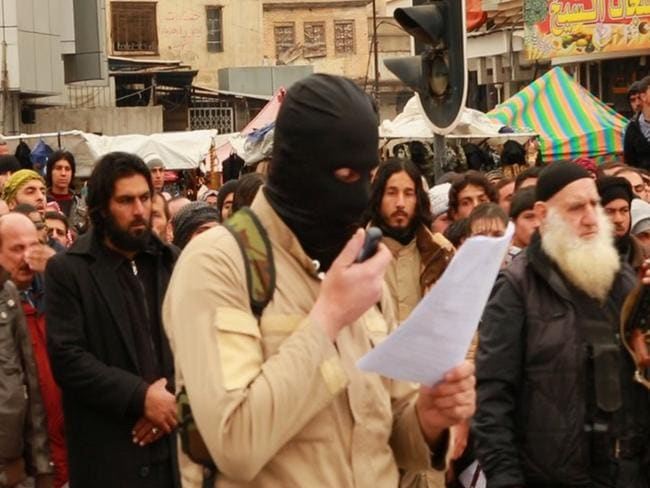 A militant reads out the charges during a public execution in Iraq.