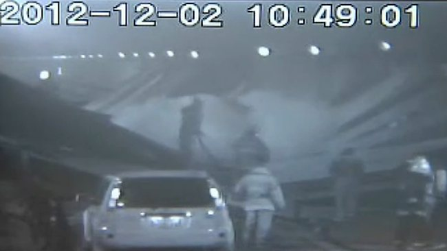 This screen grab taken from video from highway operator Central Nippon Expressway Company Limited shows rescue workers backing off as part of the roof collapses (centre) during operations to rescue people trapped in their cars. Picture: AFP/ Central Nippon Expressway Company Limited