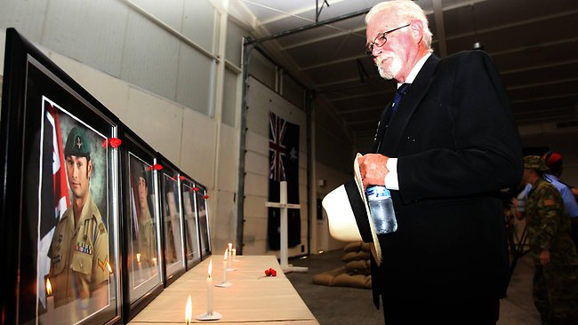 David McCarthy, father of killed digger Signaller Sean McCarthy walks past the photos of the five fallen diggers at Al Minhad Air Base in the United Arab Emirates. Picture: Gary Ramage