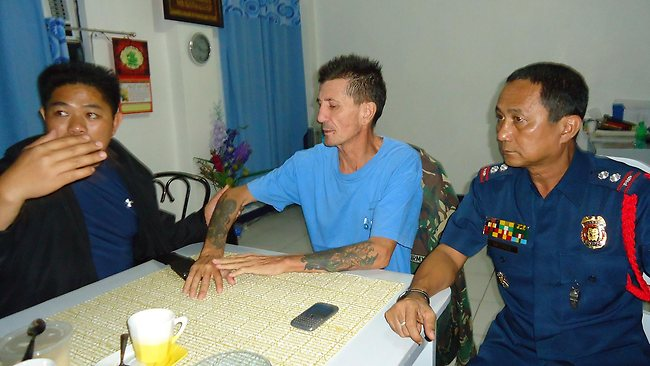 Kidnapped Australian national Warren Rodwell (C) sits next to Philippine police superintendent Jilius Munez (R) at the police station in Pagadian City in southern island of Mindanao early March 23, 2013 shortly after his release. Islamic militants in the Philippines have released Rodwell, more than 14 months after kidnapping him from his home in the south of the country, the military said on March 23. AFP PHOTO/Jong Cadion