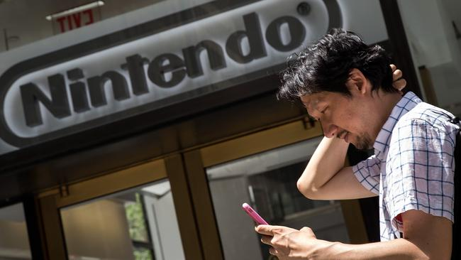 A man plays Pokemon Go on his smartphone outside of Nintendo's flagship NYC store. Picture: Drew Angerer