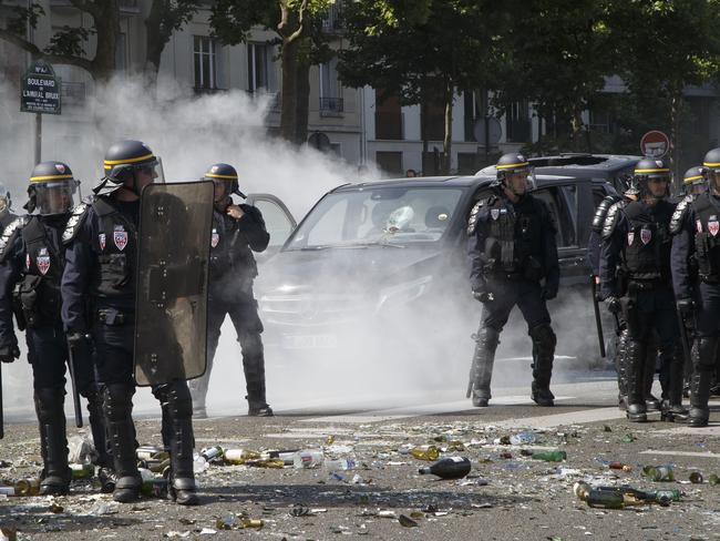 Police officers stand next to a burned out car during a taxi driver demonstration in Paris. Picture: AP/Michel Euler
