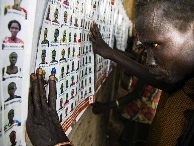 People from Thonyor, South Sudan, examine photographs of former residents now living in camps.