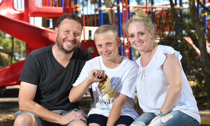 Mark, Jesse and Alice Pannenburg pose for a photograph at Edwardstown Primary school, Adelaide on Friday the 2nd of March 2018. Jesse is having his hair shaved off at the school assembly, in aid of Childhood Cancer research. His little sister Holly would be just starting school now, but she died from cancer at 11 months. The school is also naming a playground after her. (AAP/ Keryn Stevens)