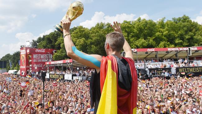Bastian Schweinsteiger holds up the trophy to fans as they celebrate in Berlin.