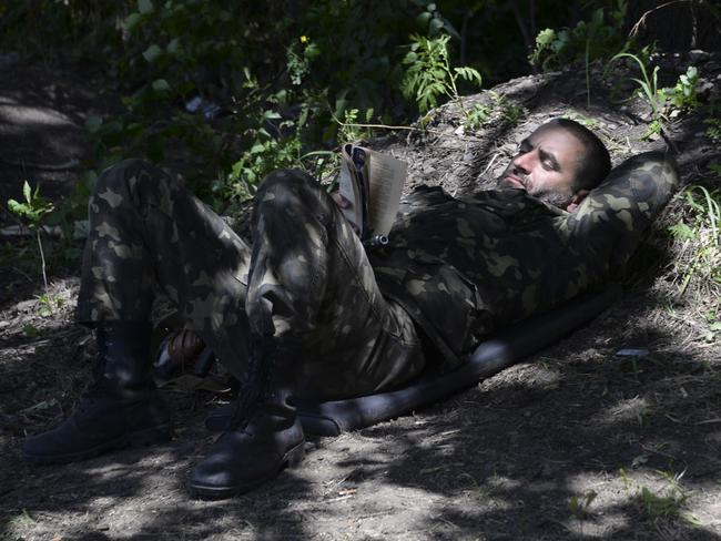 Resting on job ... A Ukrainian army soldier reads a book at a check-point near a city of Slovyansk, Donetsk region, eastern Ukraine.
