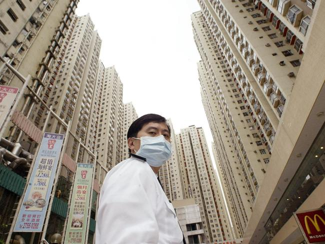Urban jungle ... A security guard wears a mask in Hong Kong where an apartment block was quarantined.