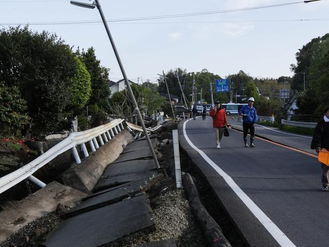 People walk along a road destroyed by an earthquake in Kumamoto, Japan. Picture: Taro Karibe/Getty Images.