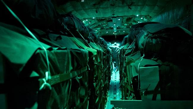 Parachute delivery ... pallets of humanitarian aid are loaded onto the RAAF plane.
