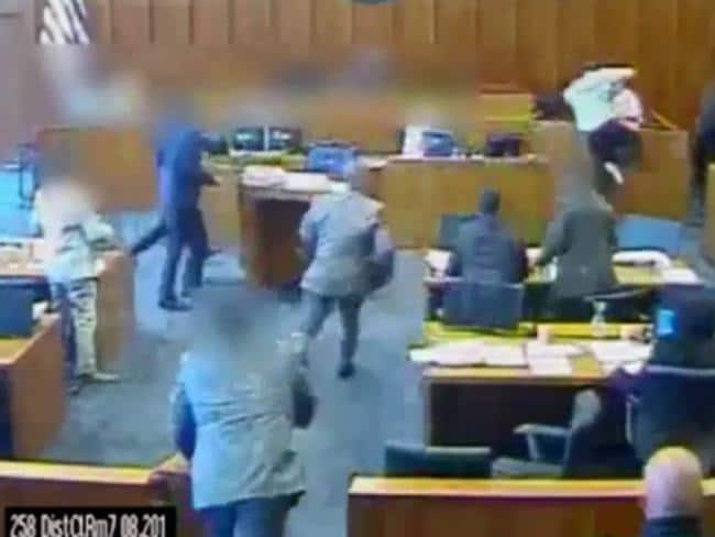 A Crips gang member leaps into the witness stand armed with his lawyer's pen before being shot dead by court marshall. Picture: CCTV / The Sun