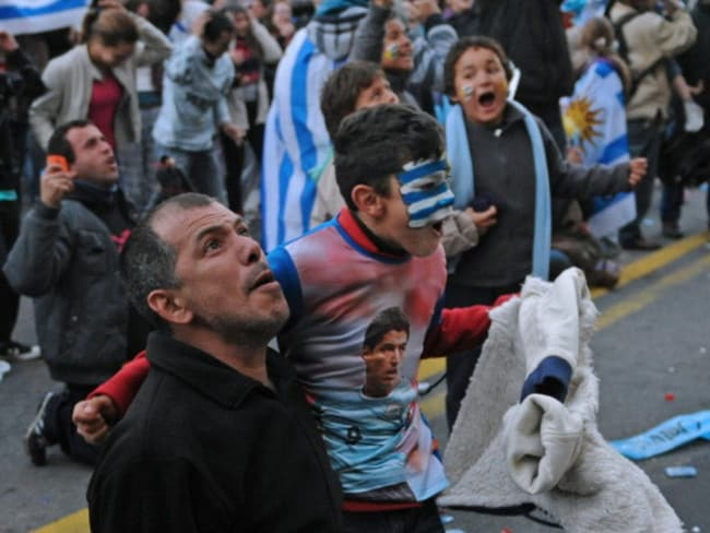 Uruguay fans celebrate as they watch the FIFA World Cup 2014 match against England on a giant screen at Montevideo's main avenue 18 de Julio.