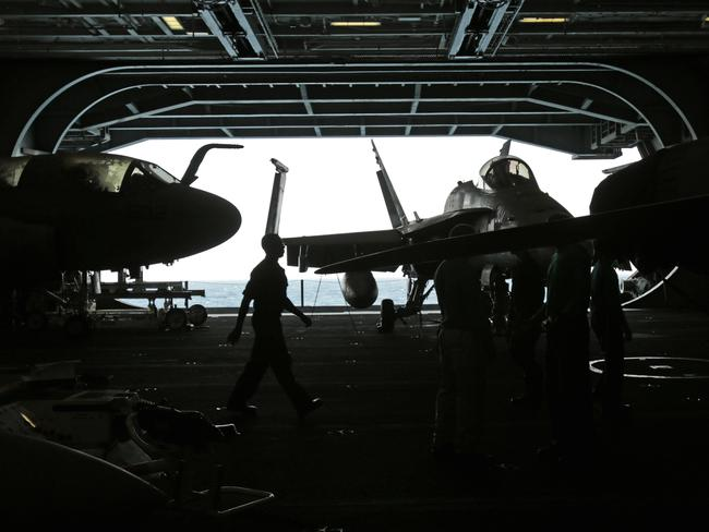 All aboard ... Aircraft in the hangar deck of the US Navy aircraft carrier USS George H.W. Bush in the Persian Gulf, yesterday. Source: AP