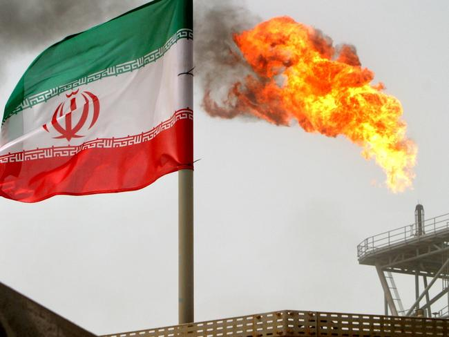 A gas flare on an oil production platform in the Soroush oil fields is seen alongside an Iranian flag in the Persian Gulf. Picture: Reuters