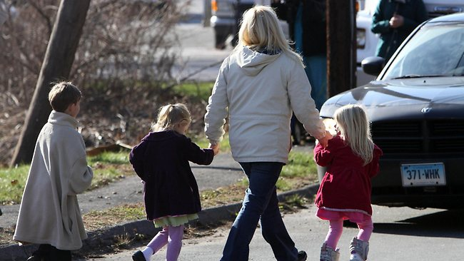 Parents walk away from the Sandy Hook Elementary School with their children following a shooting at the school. Picture: AP