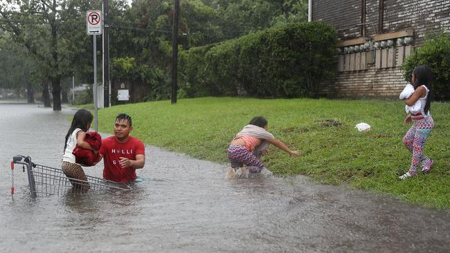 A man helps children across a flooded street as they evacuate their home. Picture: Joe Raedle/Getty Images/AFP