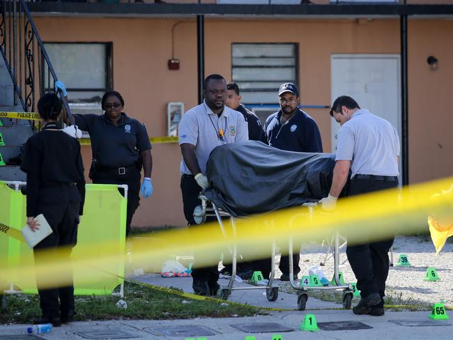 Shot ... The body of Kevin Richardson, 30, is carried out from an apartment complex in Miami's Liberty City neighbourhood. Picture: Getty