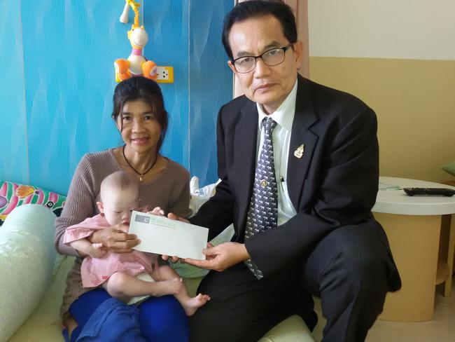 Worldwide concern ... Hands Across The Water's Nom Manochantr presents a cheque to baby Gammy and her grandmother inside Samitivej Hospital, Bangkok. Picture: Getty Images)