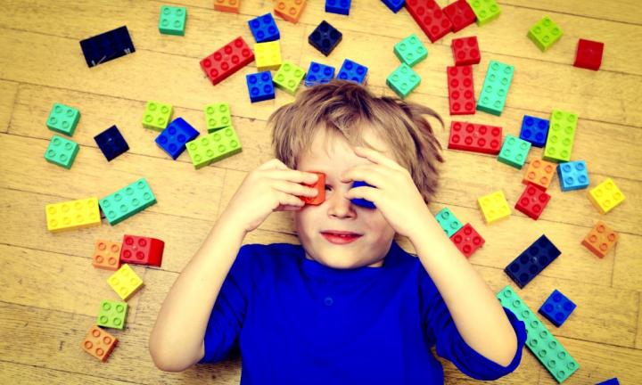 child playing with colorful plastic blocks indoor, early learning
