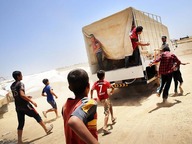 Children at the Khazair displacement camp chasing a Red Crescent society truck delivering food and other items on June 30.