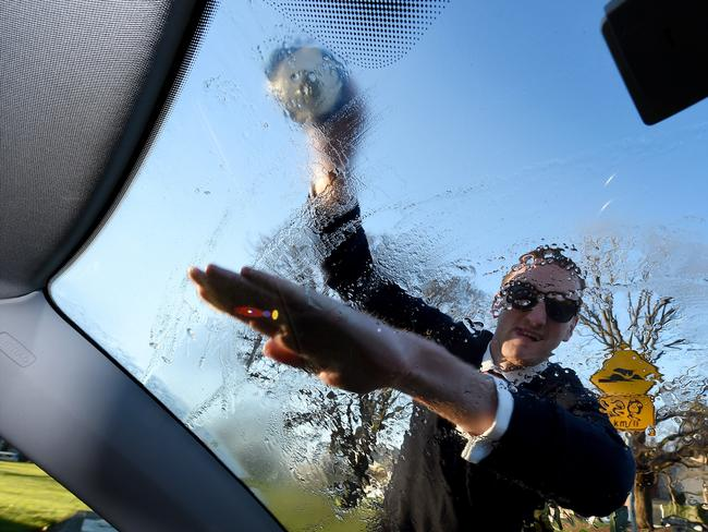 Callum Wood from Carlton puts water on his windscreen to get the ice off after a cold winter's night. Picture: Nicole Garmston