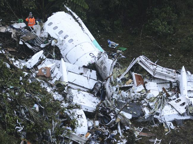 Rescue workers stand at the wreckage site of a chartered aeroplane that crashed outside Medellin, Colombia. Picture: AP