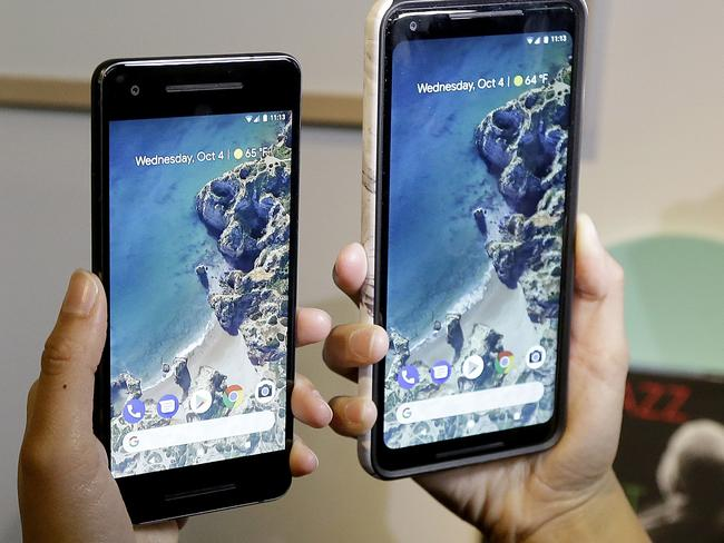 A woman holds up the Google Pixel 2 phone, left, next to the Pixel 2 XL phone at a Google event in October. Picture: Jeff Chiu
