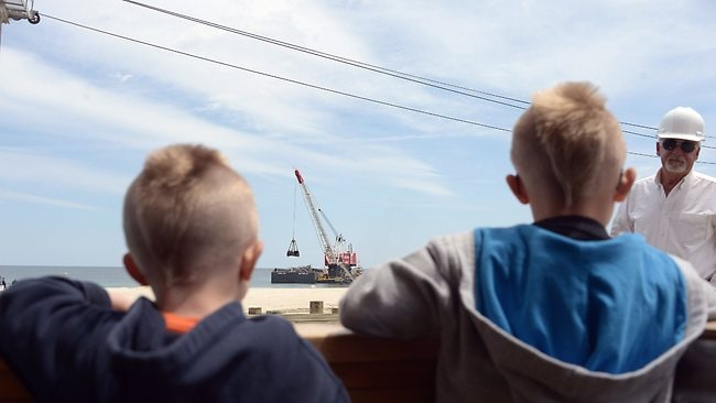 Two young boys talk to a shore worker while a crane demolishes the JetStar roller coaster. Picture: Getty Images/AFP