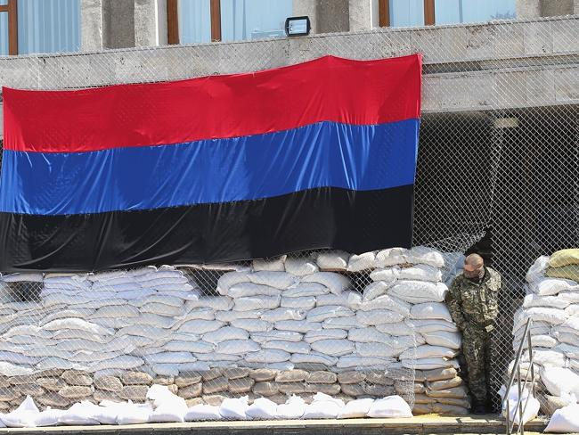 Keeping watch ... a pro-Russian militant looks out from the barricaded entrance of the city council building in Slovyansk, Ukraine.