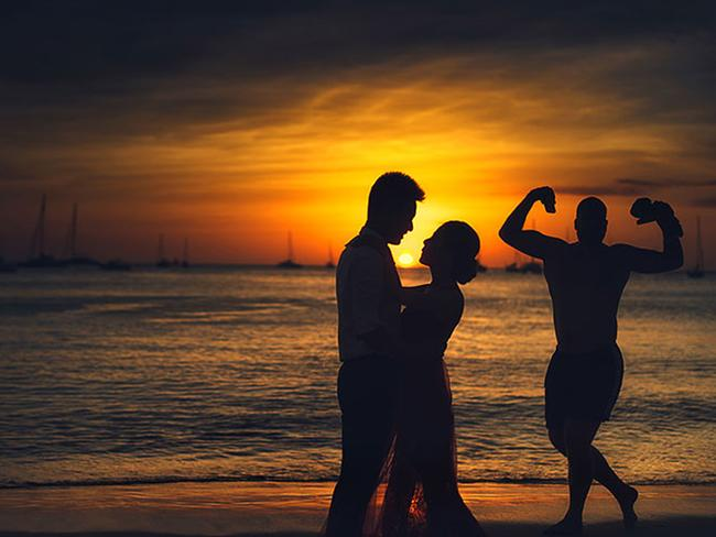 This photobomb is quite special. Sunset? Check. Silhouette? Check. Muscle man doing a strong man pose? Check. Picture: BIN SHEN / CATERS NEWS