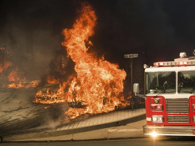 A fire truck passes burning vehicles as a wildfire rages in Ventura, California. Picture: AP Photo/Noah Berger