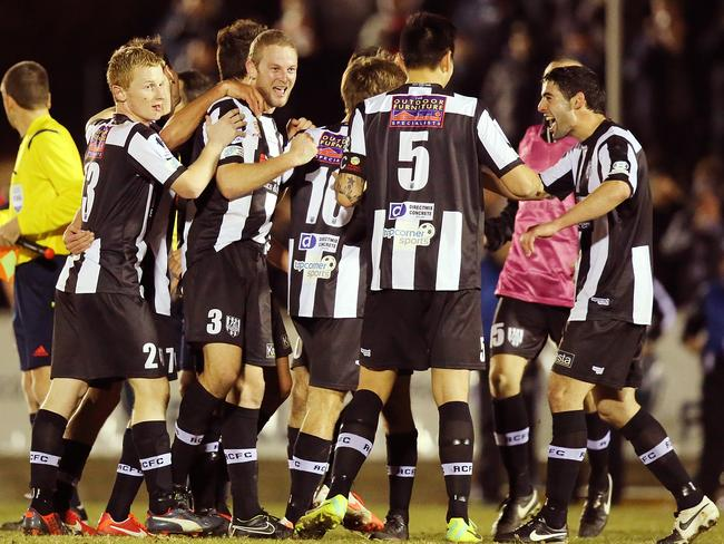 Adelaide City players celebrate after their shock win.