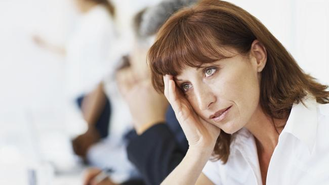 Tired female executive with hand on head during a meeting