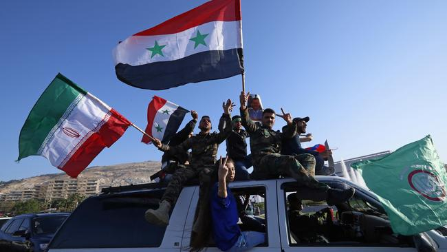 Protesters gather waving Syrian flags and victory signs. (AP Photo/Hassan Ammar)