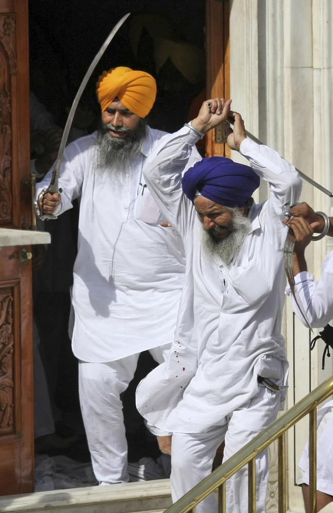 Members of a Sikh group brandish swords and wooden sticks at the Sikhs' holiest shrine in India. AP Photo/ Sanjeev Syal