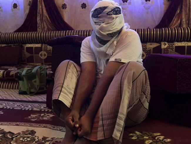 A former detainee shows how he was kept in handcuffs and leg shackles while held in a secret prison at Riyan airport in the Yemeni city of Mukalla in this May 11, 2017 photo. He covered his face for fear of being detained again. Picture: Maad El Zikry/AP