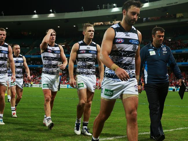 Geelong players including captain Joel Selwood (3rd from R) and coach Chris Scott (R) walk from the ground after their 100 plus point loss. Picture: Toby Zerna