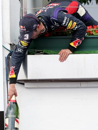 Daniel Ricciardo passes a champagne bottle down to his team as he celebrates the victory. Picture: Getty Images