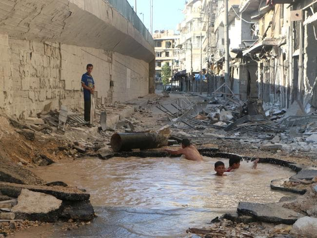 Syrian children cool off in a crater filled with dirty water.