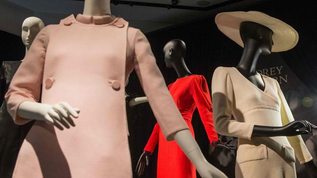 An employee poses alongside a display of outfits during a preview of Audrey Hepburn's personal collection at Christie's auction house in central London on September 22, 2017. / AFP PHOTO / Daniel LEAL-OLIVAS
