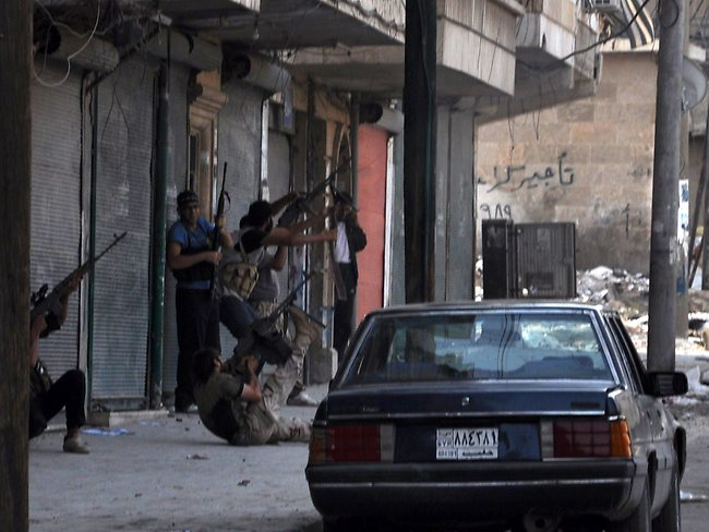 Rebels fighters take their position along a street in the Salaheddin district of the restive Syrian city of Aleppo.