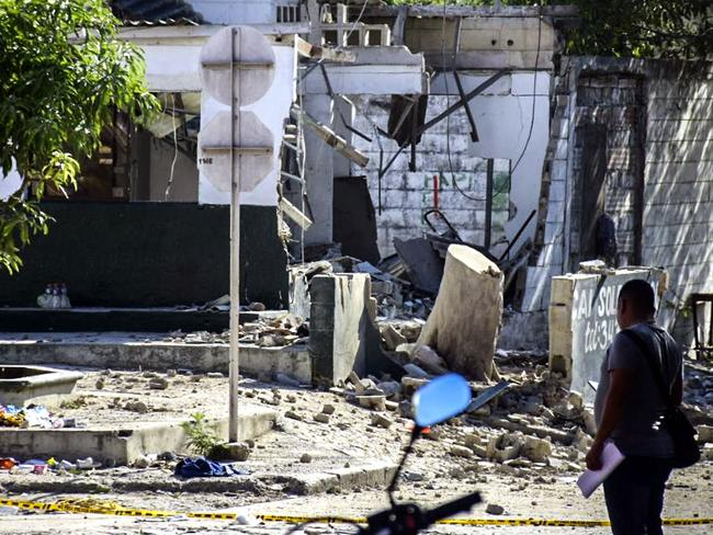 A man walks in front of the police station where five died and 41 were wounded during a series of bomb attacks. Picture: AFP Photo/Jose Torres