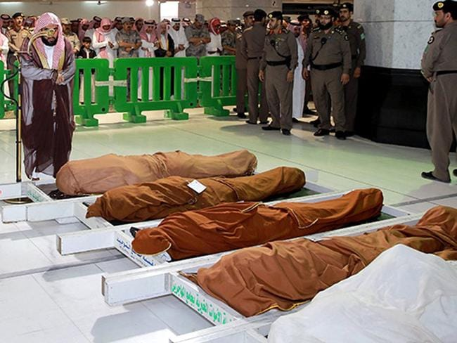 A cleric and mourners pray in the holy mosque in Mecca during the funeral of three Saudi guards who died in the early January suicide bombing. (Another two bodies were of people who died in other circumstances.) Picture: AFP PHOTO / HO / SPA