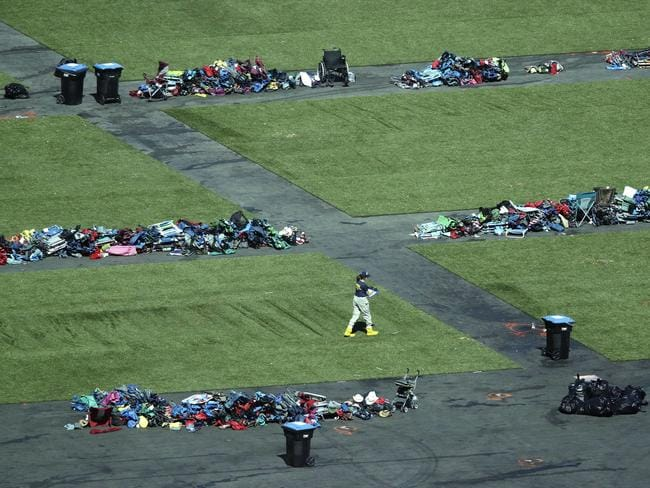 A member of the FBI walks among piles of personal items at the scene. Picture: AP
